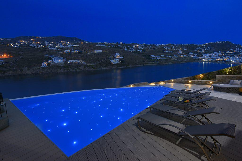 view of the starry sky above the blue sea from the illuminated pool