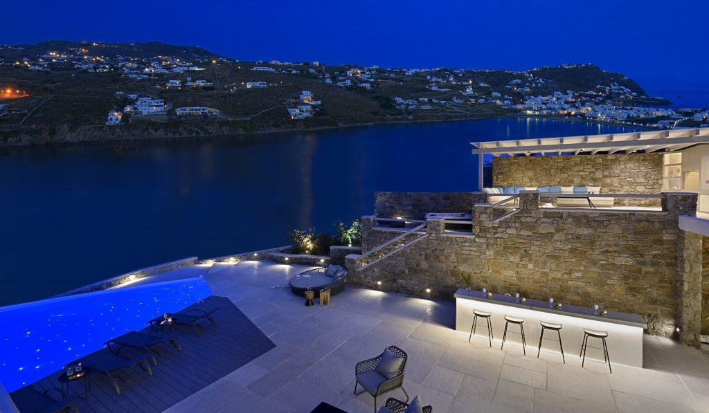 outdoor area with pool and illuminated luxury bar