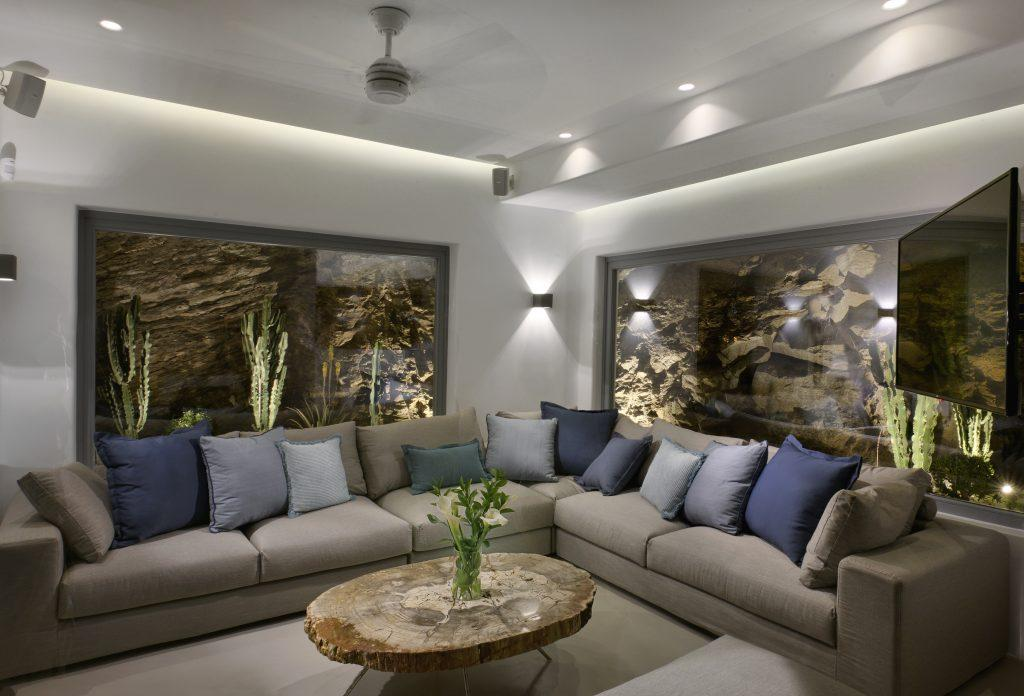 living room with white walls and comfortable large gray furniture, ideal for hanging out with friends