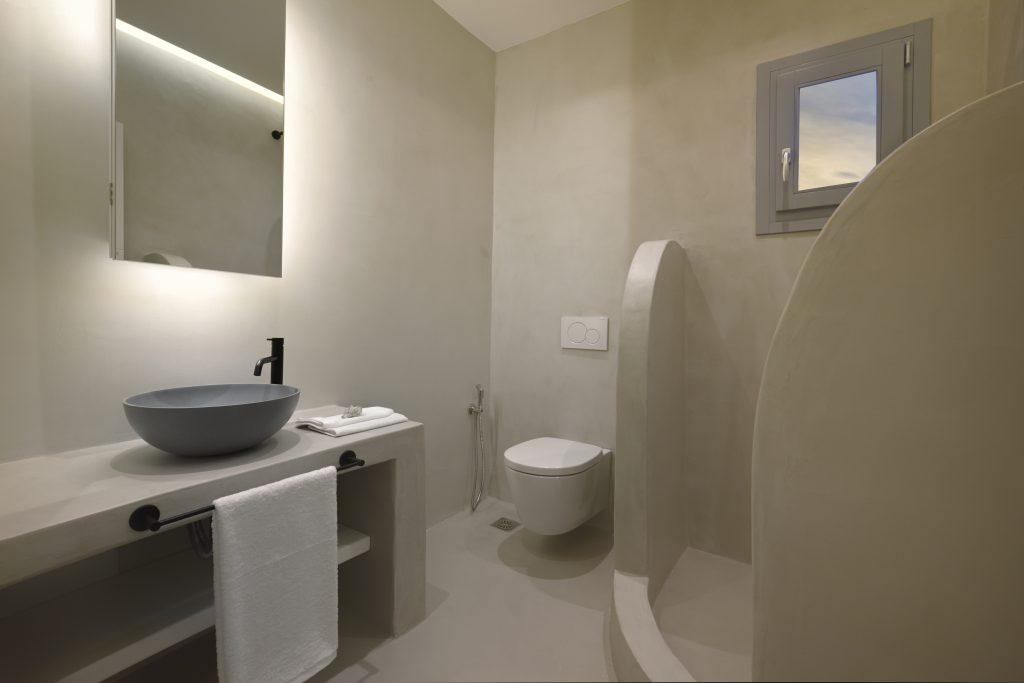 white walls of bathroom with large shower and toilet