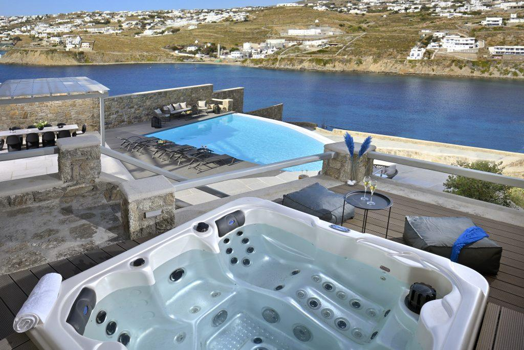 view of the crystal blue sea and the city of Mykonos from the pool