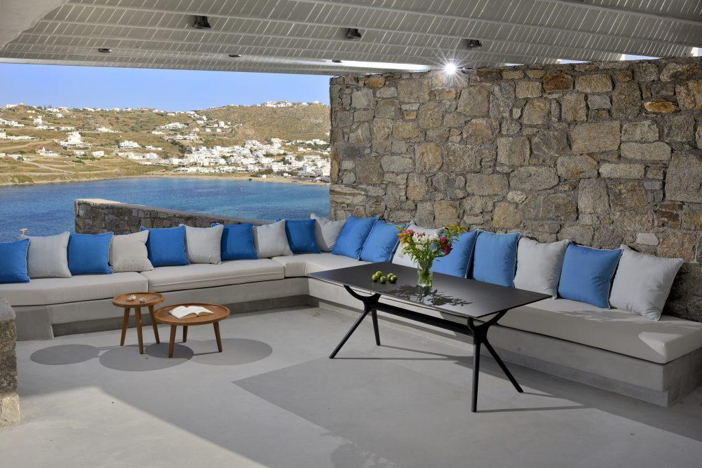 view of the blue sea and clear sky from the yard with comfortable furniture