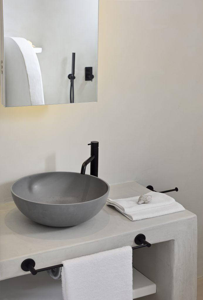 bathroom with white walls and circular gray sink
