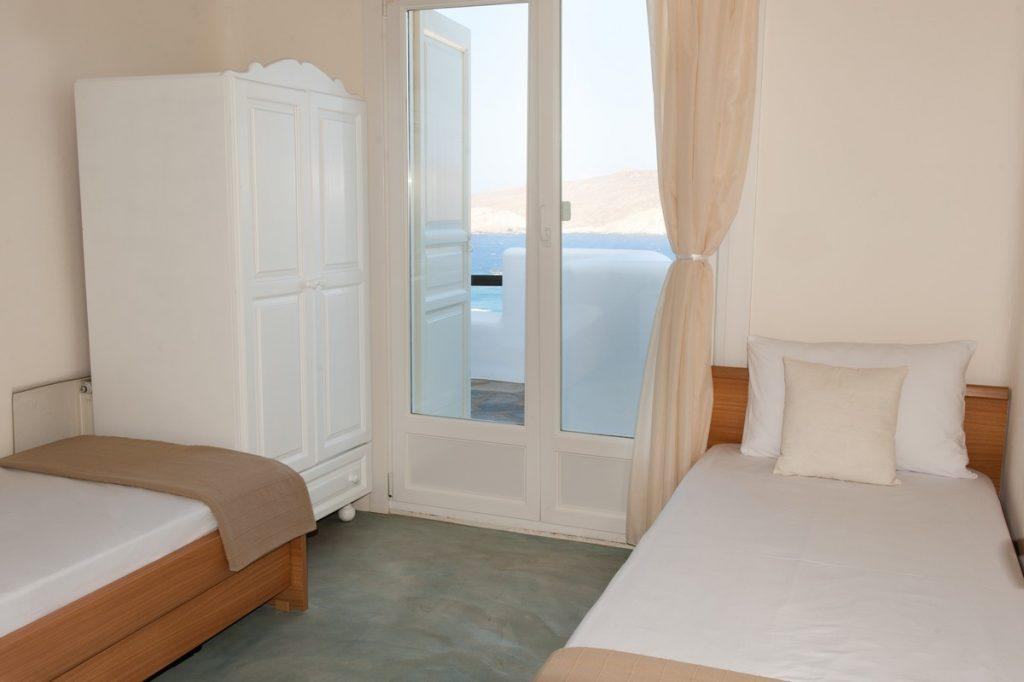 room with two comfortable beds and a stylish white wardrobe