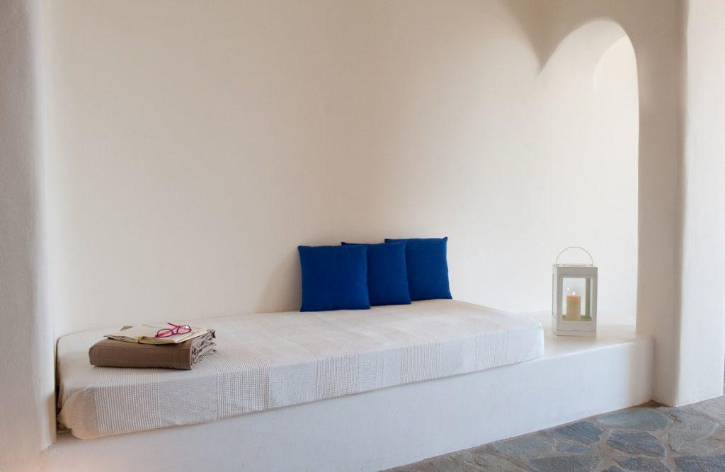 white bed with bright blue soft pillows and a lantern that contributes to a soothing atmosphere