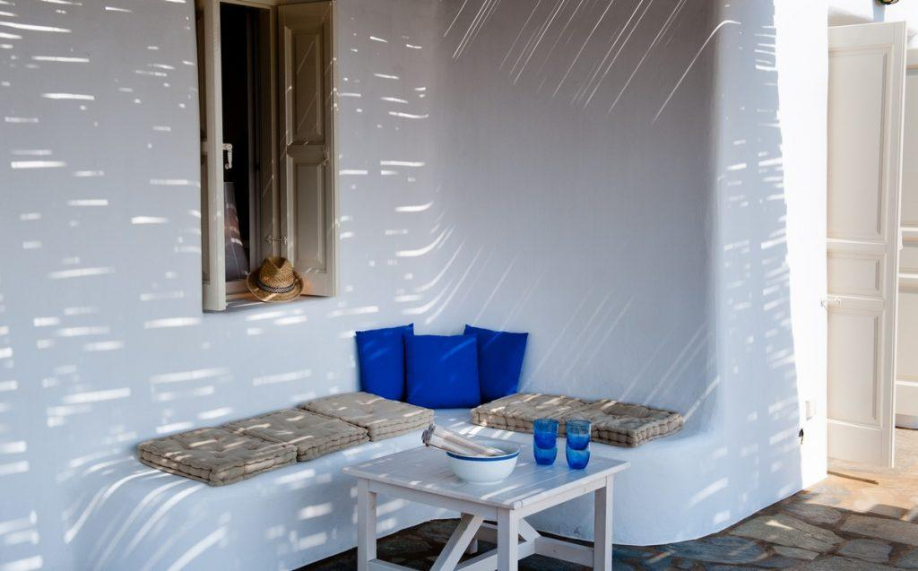 white bench with bright blue soft cushions to enjoy the shade