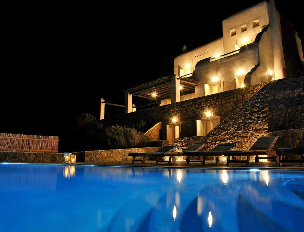 luxurious villa made of stone walls lit by lamps that emphasize its authenticity