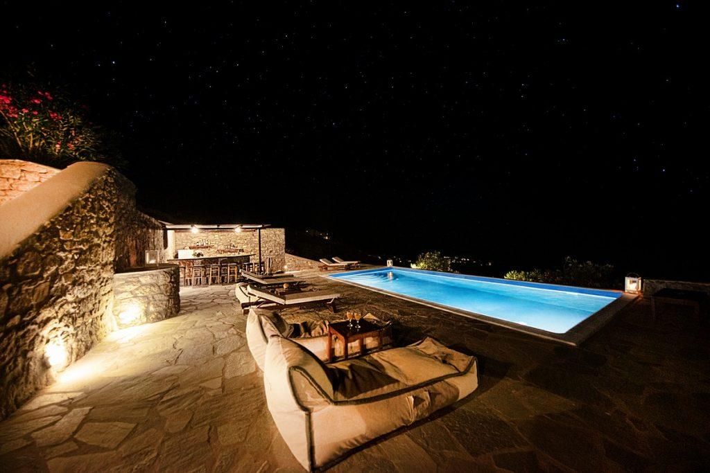 night view of the starry sky and a lighted pool for an ideal romantic evening