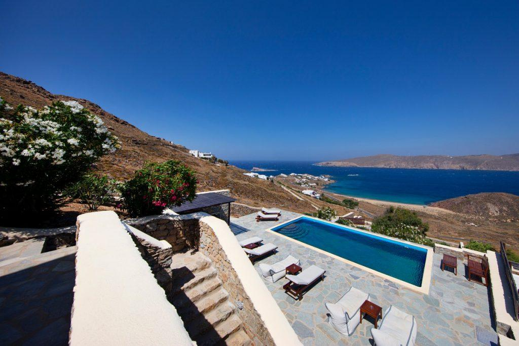 beautiful spacious courtyard of the villa with a stone staircase and wooden deck chairs by the pool