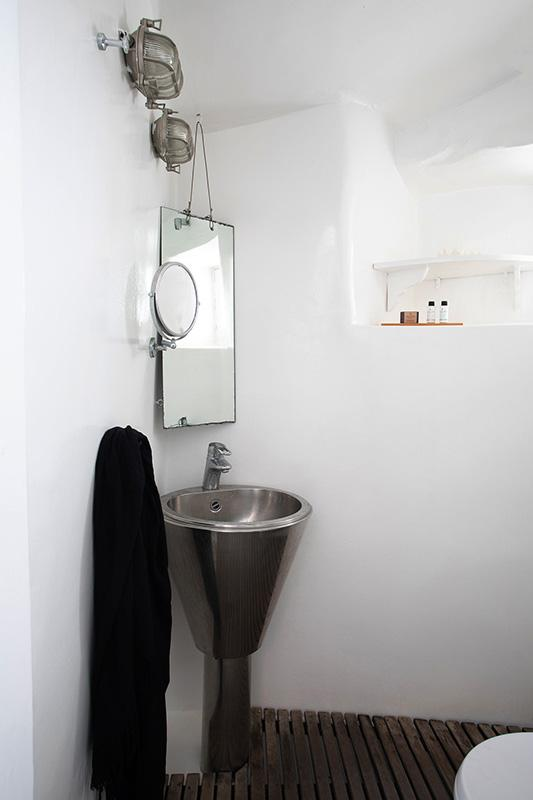 unique designed bathroom with metal sink and hanging mirror