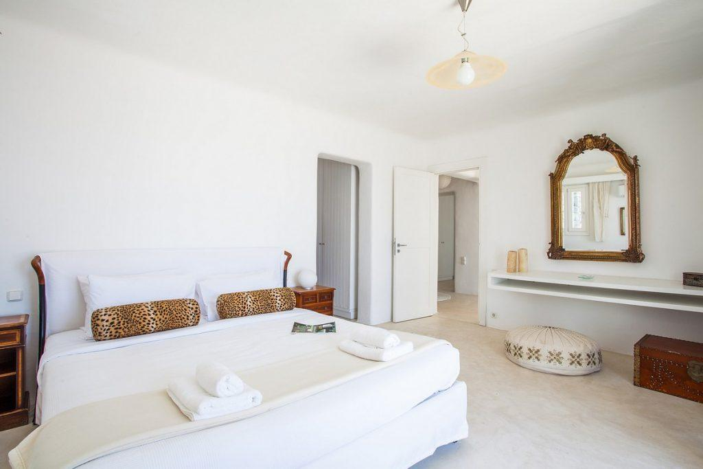 white painted master bedroom containing king size bed big mirror and decorative wooden chest