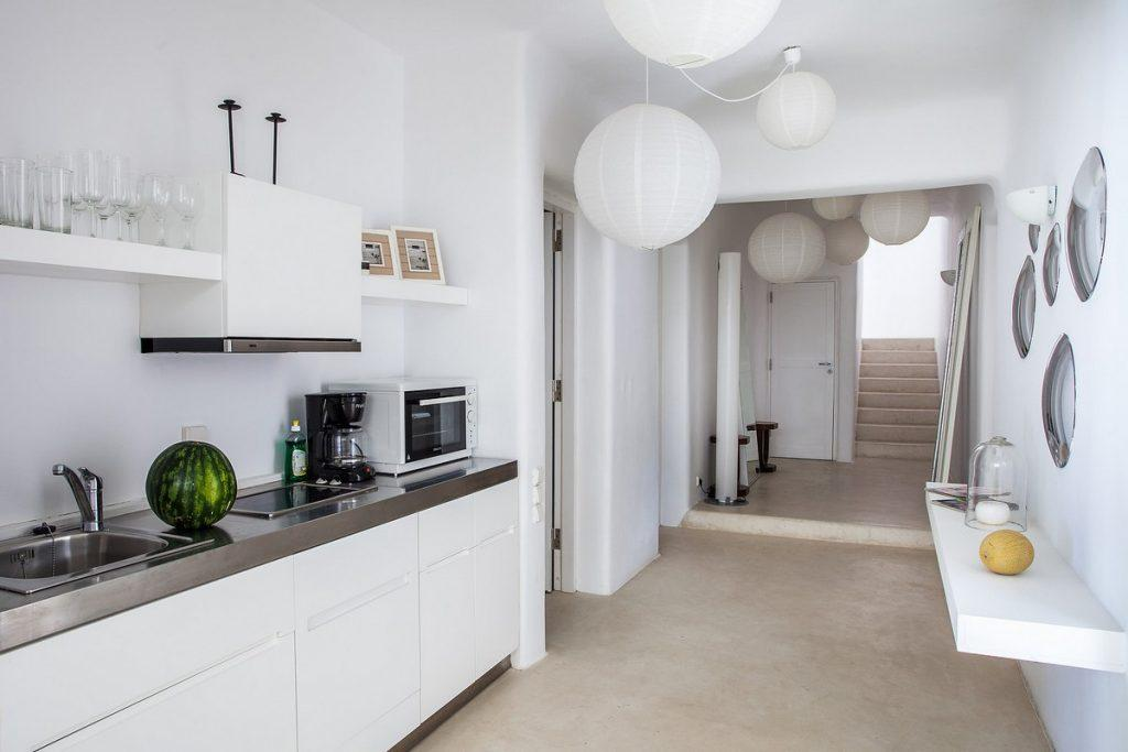 white painted kitchen with microwave coffee maker and interesting chandeliers