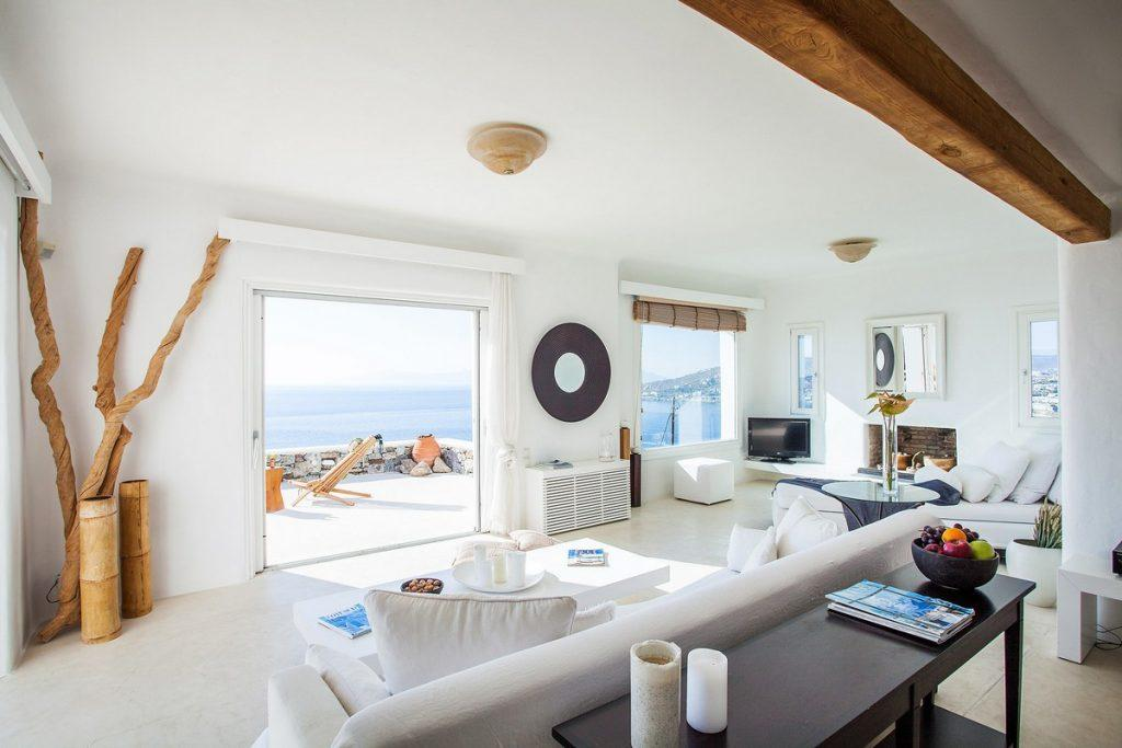 natural lightened spacious living room with big sofa faced directly at window wall sea view and balcony