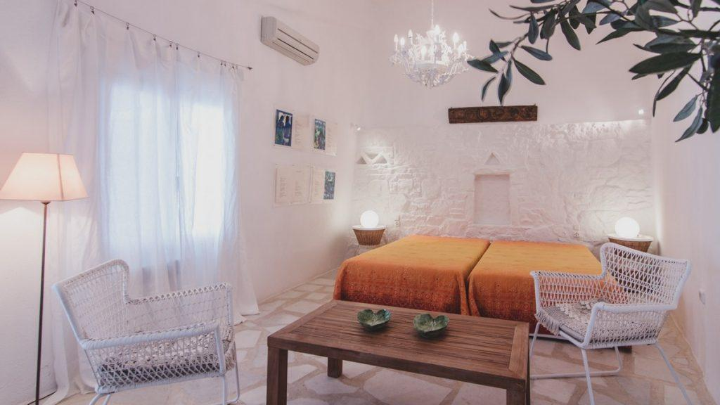 room with comfortable beds and decorative white chairs