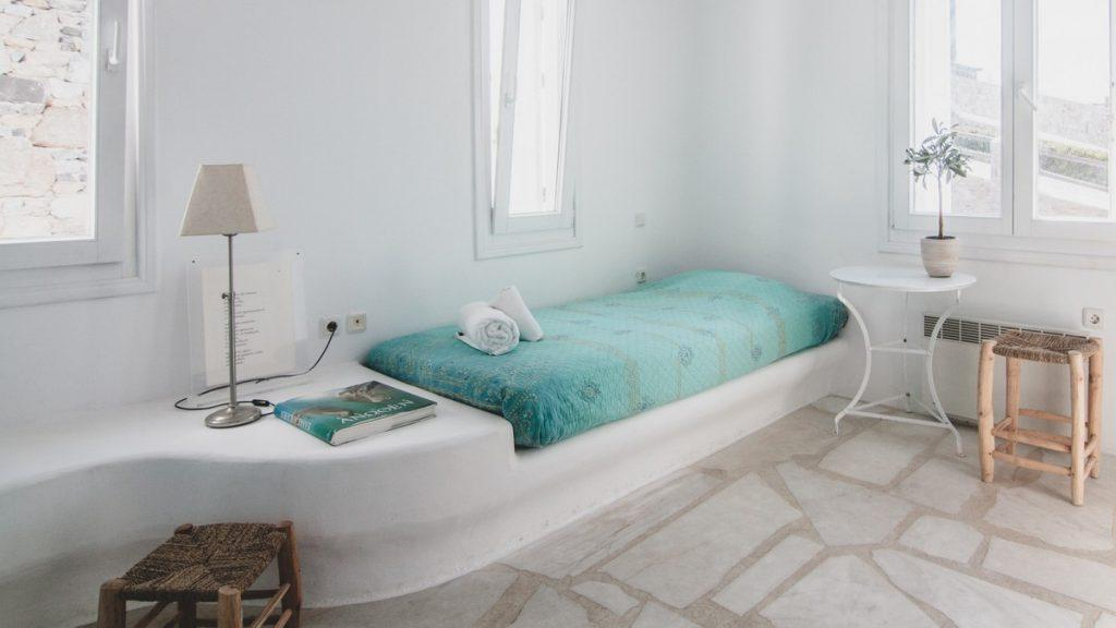 room with a comfortable bed and a white table in the corner ideal for sleeping and relaxing