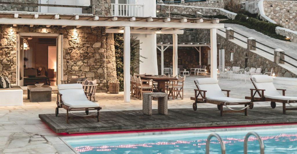 wooden deck chairs with soft white pillows ideal for enjoying by the pool