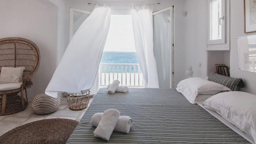 spacious room with a comfortable bed and a wicker decorative chair in the corner