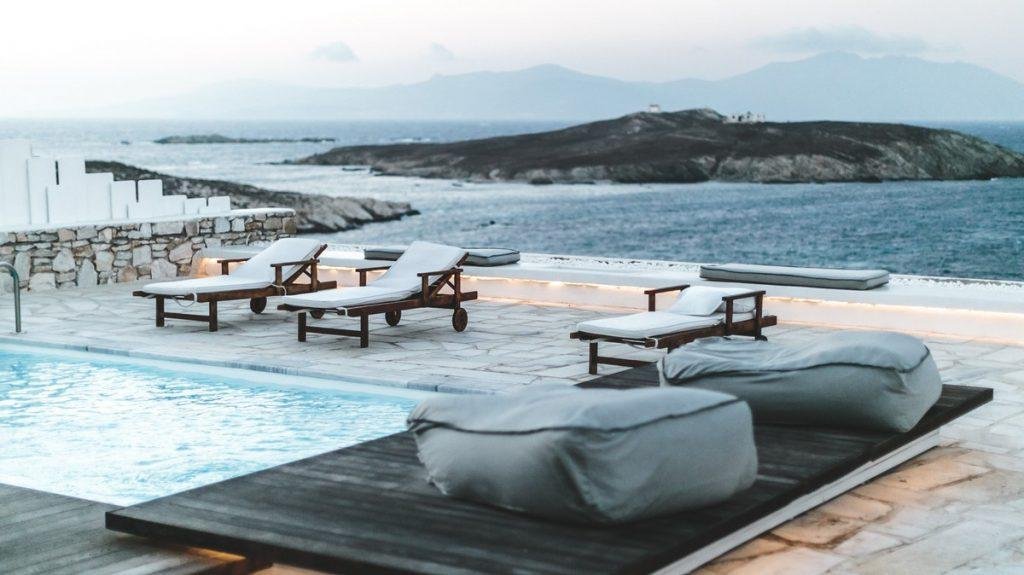 wooden deck chairs with comfortable white pillows that fit perfectly next to the stone fence