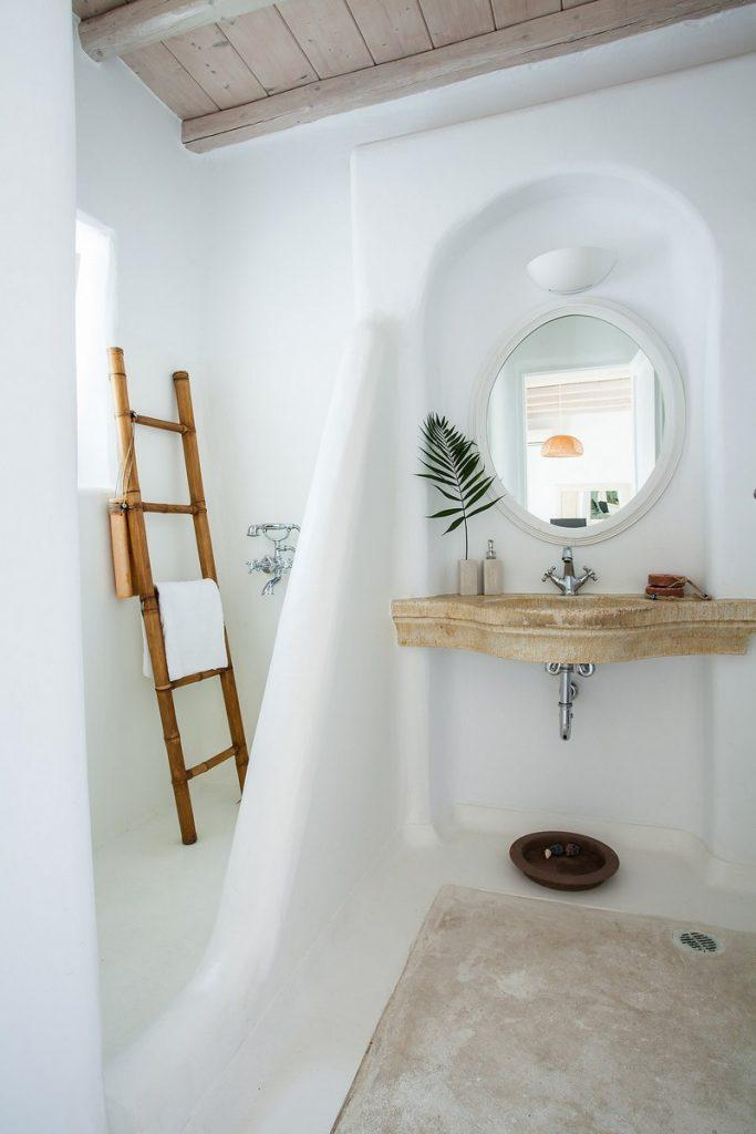 circular mirror and a sink decorated with green leaves that contribute to comfort