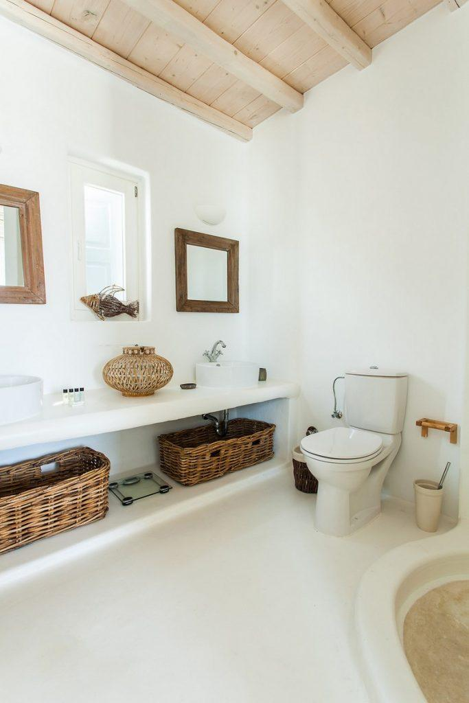 bathroom with toilet bowl and decorative wicker baskets