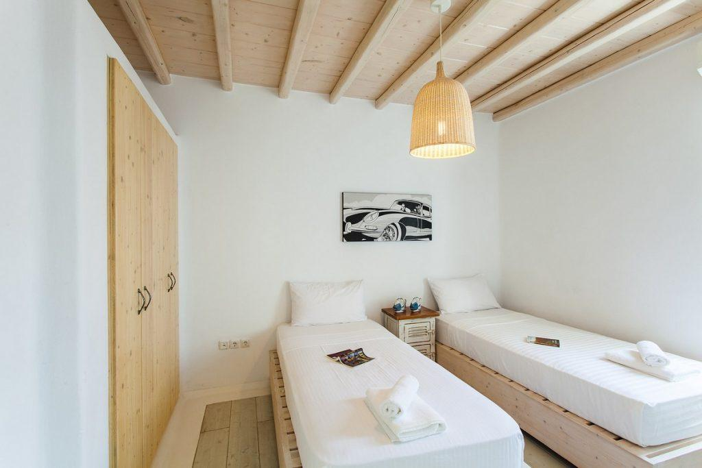 room with a large wooden closet and two comfortable beds