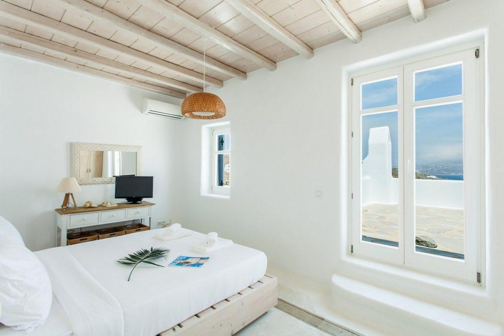 room with a comfortable bed and a decorative wood table ideal for two