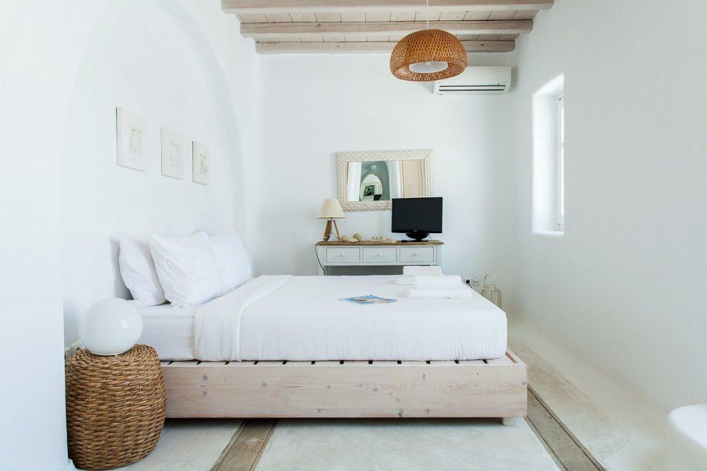 ideal bedroom for two in white tone with mirror and decorative wooden table