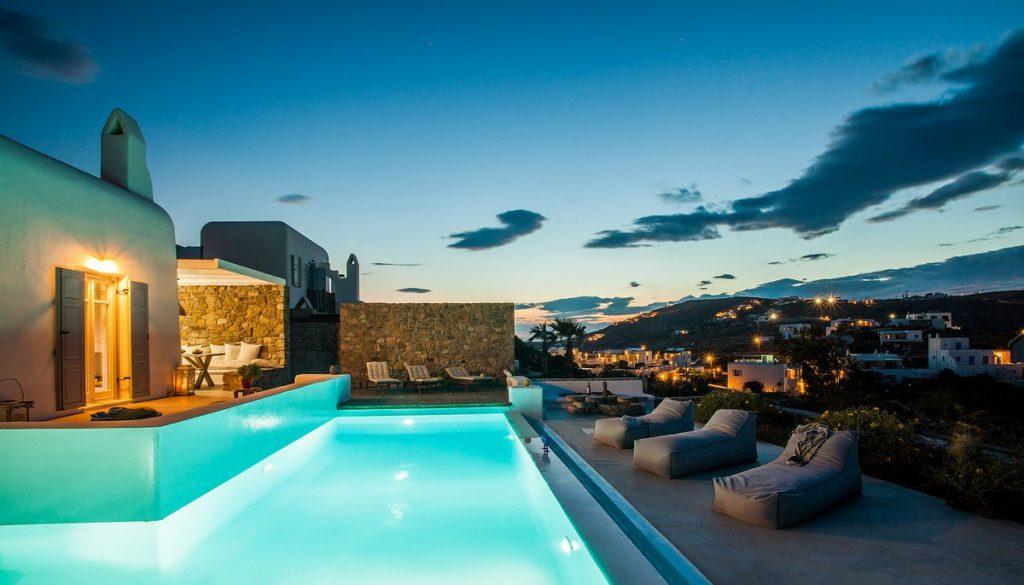 enchanting view of the illuminated city of Mykonos from a beautifully landscaped courtyard