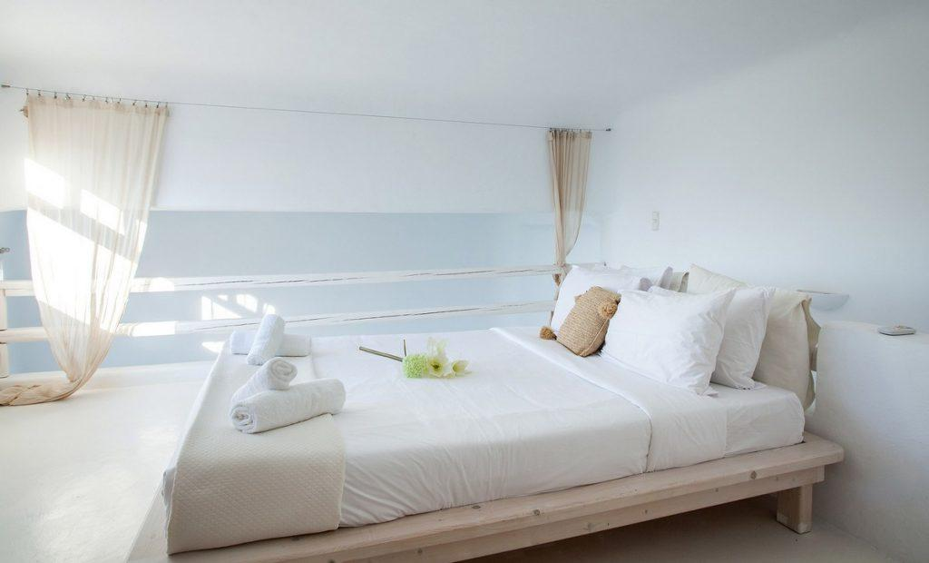 cozy king size bed with white bedding and soft pillows