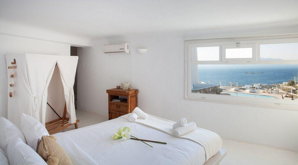ideal bedroom with a view of the glistening sea and a comfortable bed