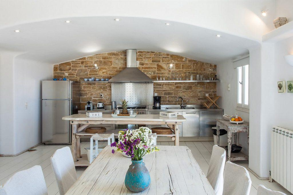 wooden white dining table decorated with flowers and a kitchen equipped with everything necessary to prepare delicious meals