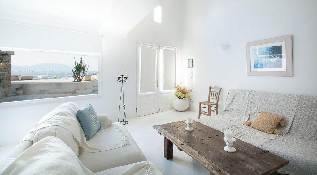 living room in white tone with a soft sofa and a wooden table decorated with flowers