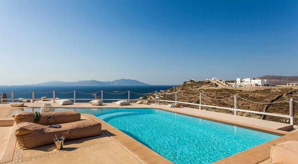 view of the blue sky and calm sea with soft pillows by the pool of pleasant water