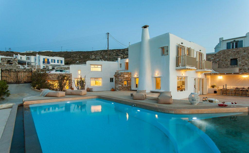 view of a white villa whose luxury is highlighted by lamps that illuminate it and a large swimming pool