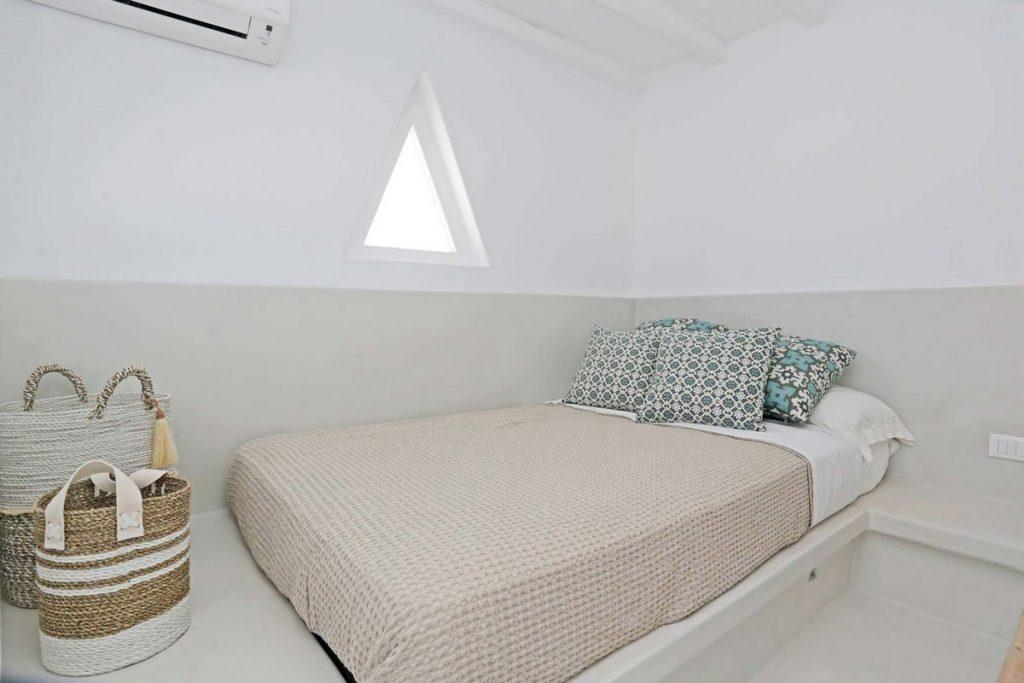 room with white walls and decorative triangular window