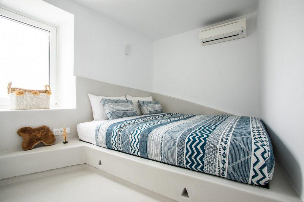 white walls of the room with a bed of colorful blue bedspreads and daylight