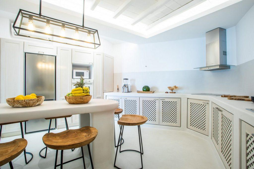kitchen with white stone table in the middle and wooden bar stools for lunch with the family