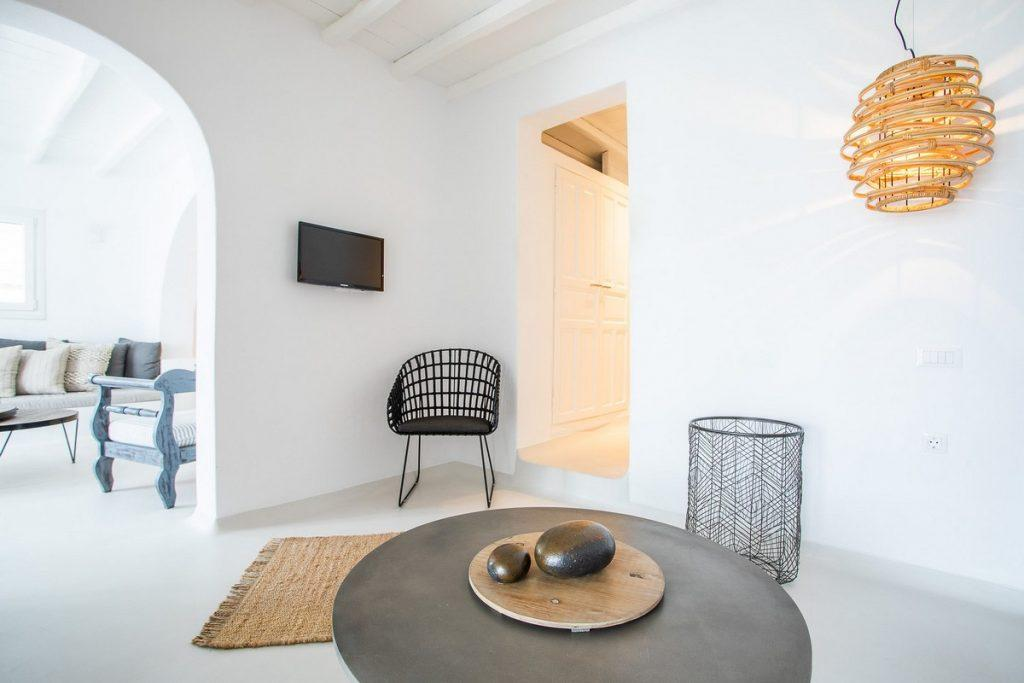 white walls of room with decorative lamp and black chair in the corner